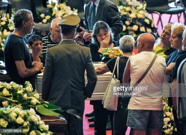 TOPSHOT Relatives mourn near the coffins of some of the victims of the collapsed Morandi highway bridge laid in front of the altar prior to the start...