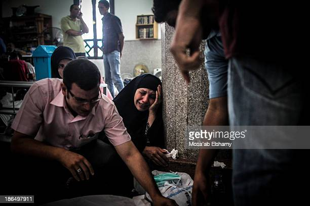 CONTENT] Relatives mourn next to dead bodies laid at Iman mosque which was turned into a makeshift morgue following the violent dispersal of Rabaa...