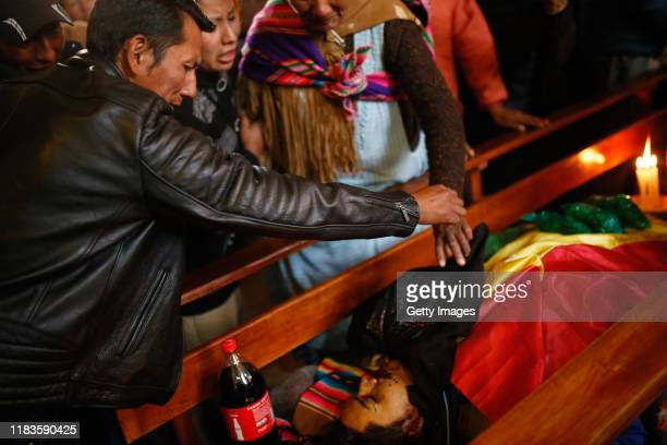 Relatives mourn next to the coffin of Clemente Mamani during the funeral of people killed yesterday during clashes between supporters of Evo Morales...