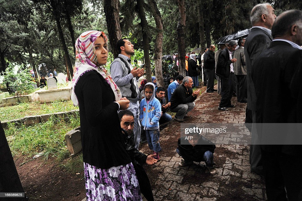 Relatives mourn on May 12, 2013 at the graves of victims of a car bomb which went off on May 11 at Reyhanli in Hatay just a few kilometres from the main border crossing into Syria. Turkey was reeling from twin car bomb attacks which left at least 43 people dead in a town near the Syrian border, with Ankara blaming pro-Damascus groups and vowing to bring the perpetrators to justice. A Syrian minister denied on May 12 accusations that Damascus was behind a bomb attack in a Turkish town that left dozens dead, a day after Ankara blamed supporters of President Bashar al-Assad for the blasts.