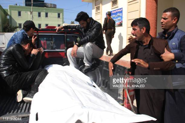 Relatives mourn over the body of a passenger who died in the ferry accident while crossing Tigris river outside a morgue in the northern Iraqi city...