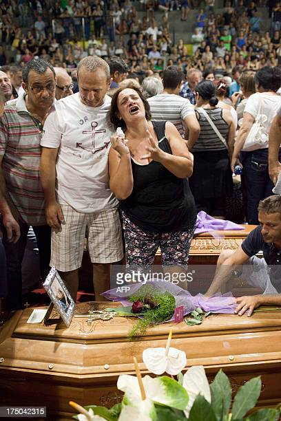 Relatives mourn victims of a bus crash on July 29 2013 in a sport hall in Pozzuoli An Italy in mourning prepared to hold a mass funeral for 38 people...