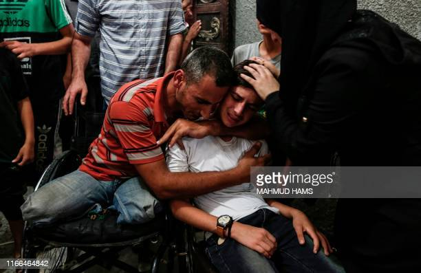 Relatives of 17-year-old Ali al-Ashqar, one of the two Palestinian youths killed yesterday by Israeli fire, mourn during his funeral at Jabalia...
