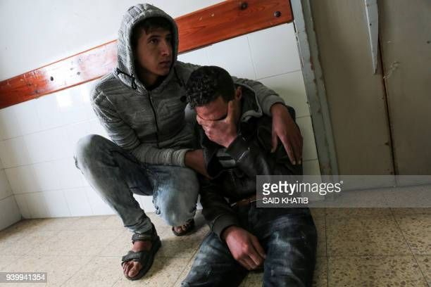 Relatives of 27-year-old Palestinian farmer Omar Samour, who was killed earlier in the day by Israeli tank fire, mourn in the hallway of the morgue...