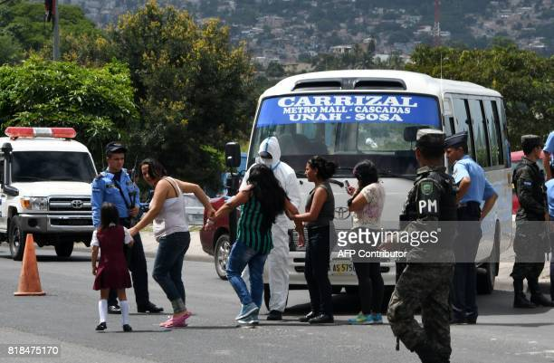 Relatives of a bus driver killed by gang members for refusing to pay them a war tax react next to the minibus in Tegucigalpa on July 18 2017 Public...
