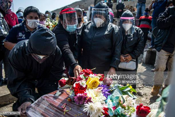 TOPSHOT Relatives of a COVID19 victim mourn during a funeral at a graveyard in Comas in the northern outskirts of Lima on August 05 2020 The pandemic...