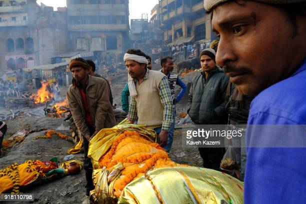 Relatives of a deceased man carry his body down the stairways of Manikarnika Ghat ready to be dipped into Ganga River for an act of purification...
