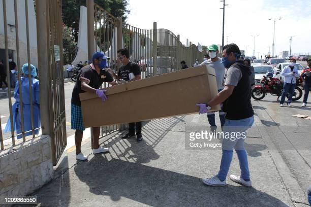 Relatives of a deceased person carry a cardboard box used as a coffin to the Jardines de la Esperanza Cemetery on April 7 2020 in Guayaquil Ecuador...