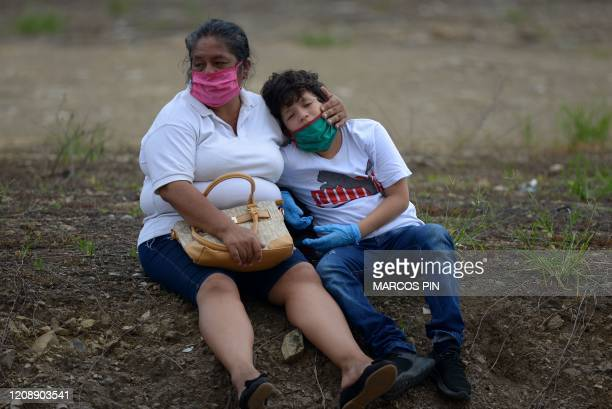 TOPSHOT Relatives of a deceased person wearing face masks mourn outside a cemetery in Guayaquil Ecuador on April 1 2020 Residents of Guayaquil in...