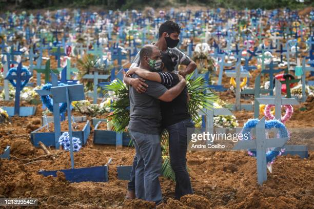 Relatives of a deceased person wearing protective masks mourn during a mass burial of coronavirus pandemic victims at the Parque Taruma cemetery on...