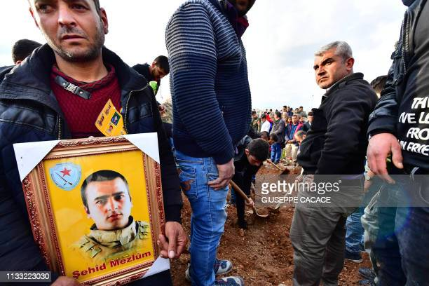 Relatives of a fighter of the Syrian Democratic Forces who was killed in an attack claimed by the Islamic State group in Manbij mourn as a grave is...