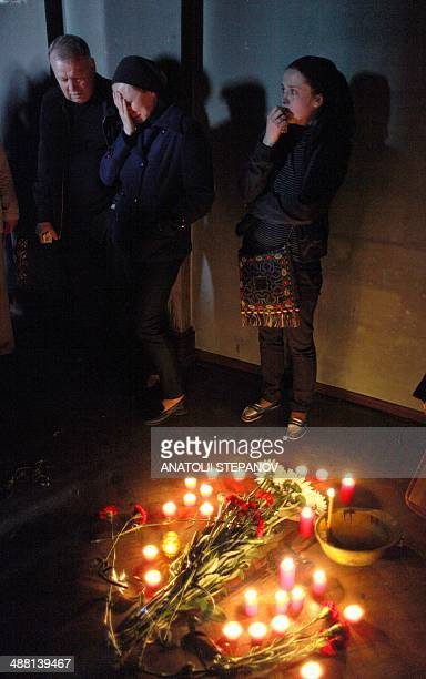 Relatives of a man killed during the fire mourn nears flowers and candles inside the burned trade union building in the southern Ukranian city of...