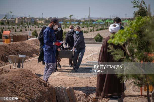 Relatives of a man who has died from coronavirus disease , carrying his dead body by a coffin in the Benhesht-e-Masoumeh cemetery in the holy city of...