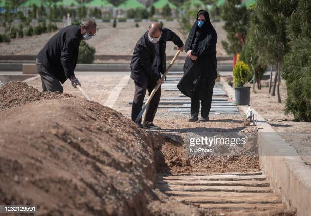 Relatives of a man who has died from coronavirus disease, cover his dead body with soil at a grave in the Benhesht-e-Masoumeh cemetery in the holy...