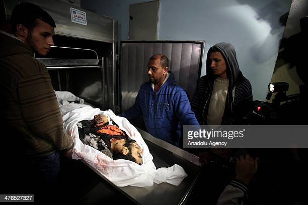 Relatives of a Palestinian man killed in an air attack staged by Israeli air forces in Beit Hanoun district take the body of the victim from morgue...