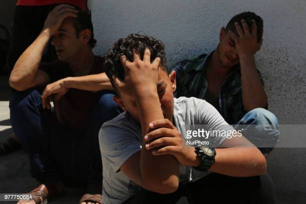 Relatives of a Palestinian Sabri Abu Khadir 24 mourns over his body at the morgue of AlShifa Hospital in Gaza City on June 18 2018 A Palestinian was...