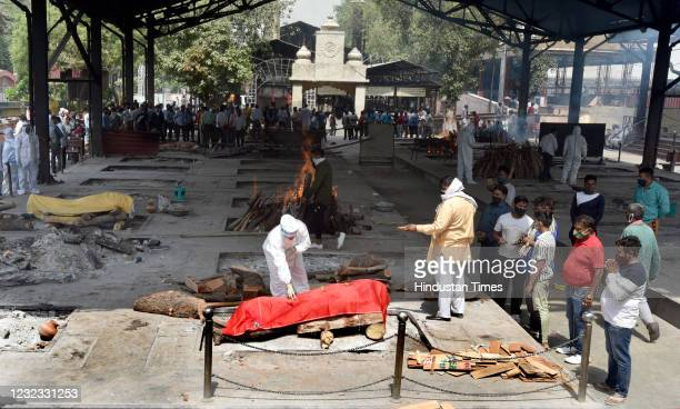 Relatives of a person who died of Covid-19 perform the last rites during cremation at Nigambodh Ghat Crematorium on April 15, 2021 in New Delhi,...