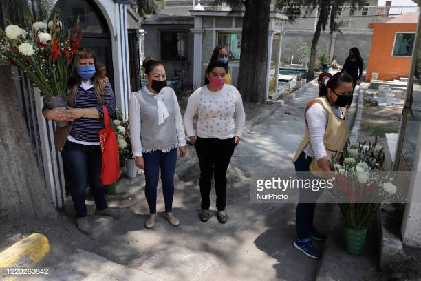 Relatives of a person who died of Covid19 suspicion visited his grave in the Pantheon of San Pedro Tláhuac Mexico City to place a cross flowers and...