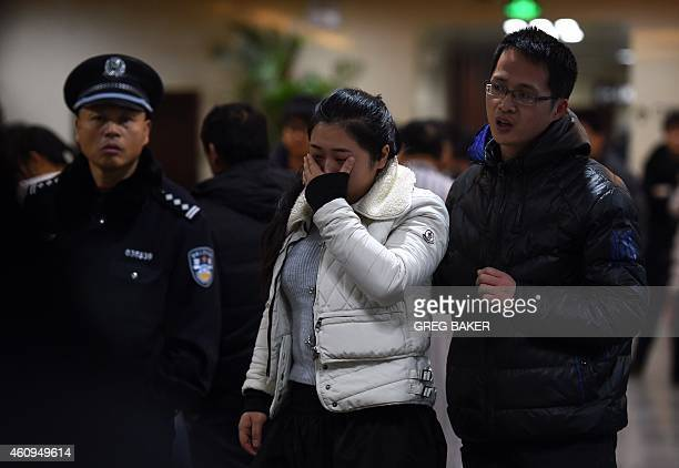 Relatives of a victim of a New Year's Eve stampede grieve as they wait with other families to identify the bodies at a hospital in Shanghai on...