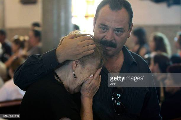 Relatives of a victim of the Casino Royale mourn as they attend a mass for the commemoration of the first anniversary of the crime in Monterrey,...