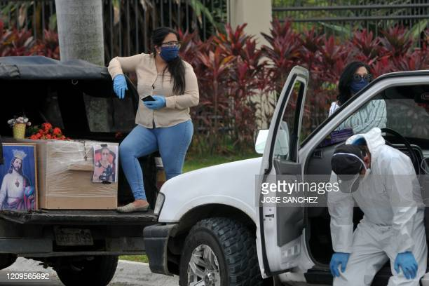 Relatives of a victim of the novel coronavirus COVID-19, arrive with the cardboard coffin of their diseased loved one at the Paque de la Paz cemetery...