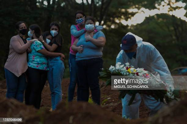 Relatives of a victim of the novel coronavirus disease COVID-19 mourn as their loved one is buried at the Vila Formosa cemetery in Sao Paulo, Brazil,...