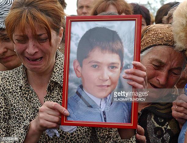 Relatives of a victim of the terrorist attack cry near a coffin during his funeral in Beslan North Ossetia 05 September 2004 The first funerals for...