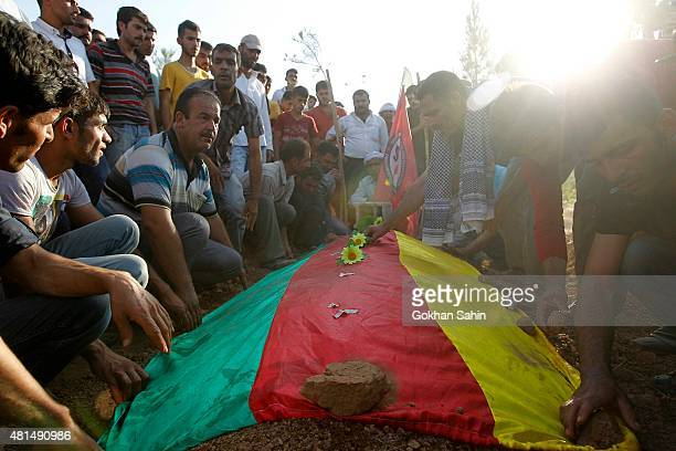 Relatives of a victim who was killed in Monday's bomb blast mourn during a funeral ceremony at a cemetery on July 21 2015 in Suruc Turkey The bomb...