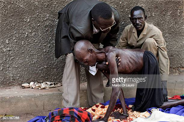 Relatives of a woman that suffer of malnutrition help her to stand on her knees at the AMREF managed PHCC on February 9 2011 in Tali Terekeka County...