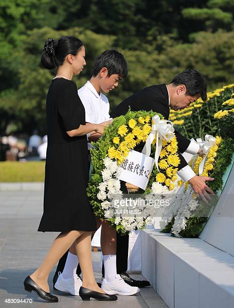 Relatives of Abomb victims offer flower wreaths on an altar during the 70th memorial service for the Abomb victims at the Peace Memorial Park in...