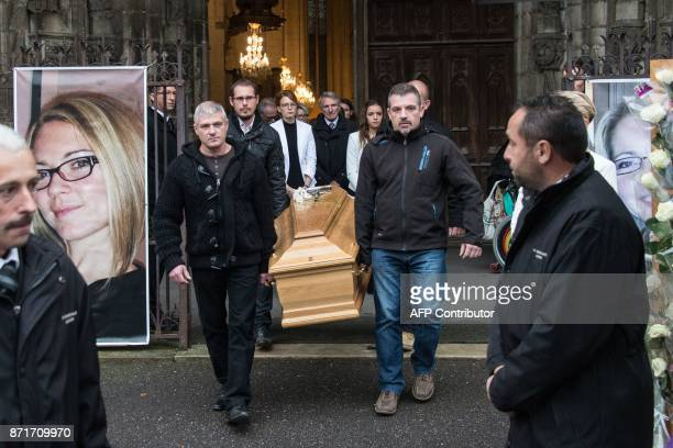 Relatives of Alexia Daval hold her coffin from the entrance of the basilica Notre Dame in Gray at the end of her funeral on November 8 next to a...