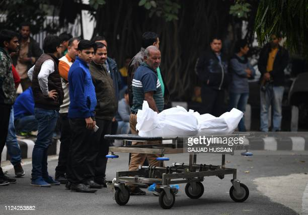 Relatives of an Indian hotel staff member who died in an early morning fire at the property look at his wrapped up body after it was handed over from...
