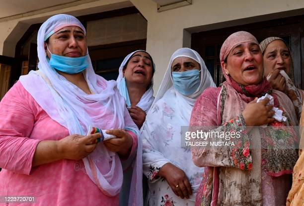 Relatives of Bashir Ahmed, a civilian who died during a gun-battle between government forces and suspected militants, mourn at Bashir's home during...