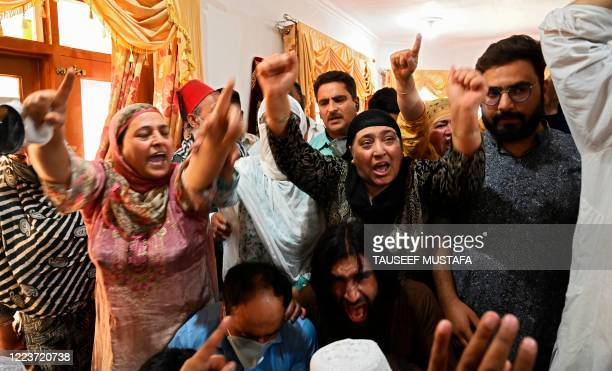Relatives of Bashir Ahmed, a civilian who died during a gun-battle between government forces and suspected militants, shout pro-freedom and...