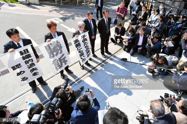 Relatives of children killed in the 2011 tsunami hold signs praising the Sendai High Court's ruling on April 26 2018 in Sendai Miyagi Japan The high...