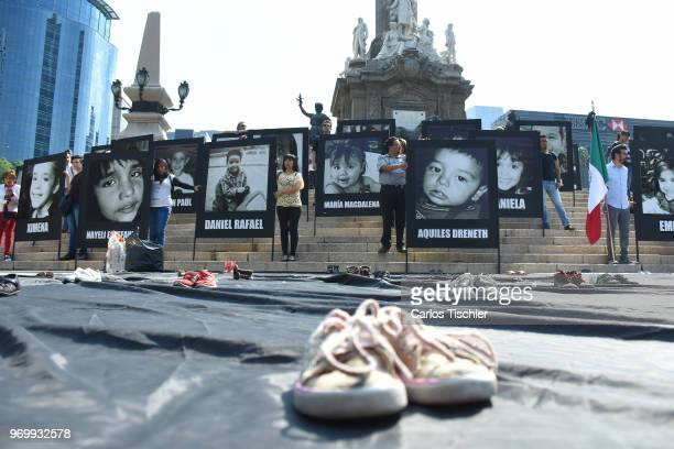 Relatives of children who lost their lives display photographs during a protest to demand justice in the 9th anniversary of the ABC day care fire...