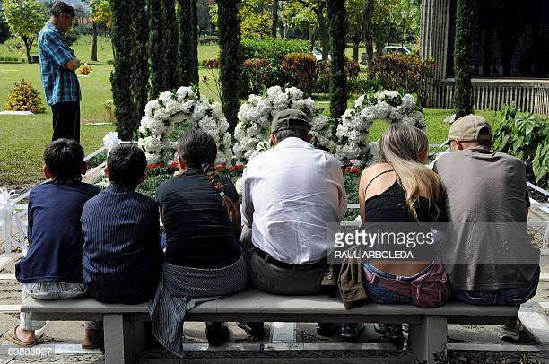 Relatives of Colombian drug lord Pablo Escobar, pray next to his tombstone on December 2 in Medellin, Antioquia department, Colombia, on the 15th...