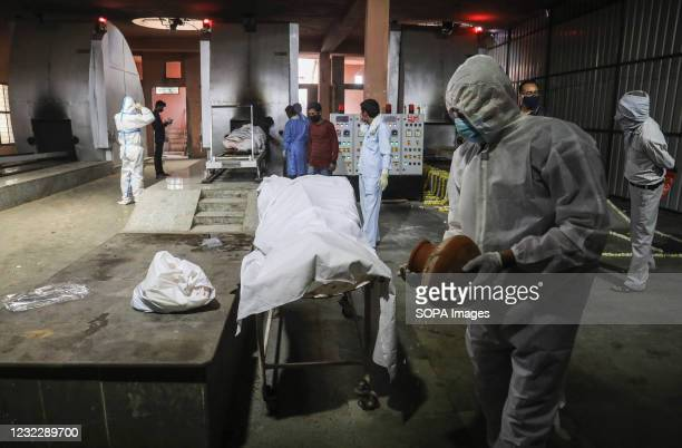 Relatives of COVID victims pay their last respect before cremation in a CNG furnace at Nigambodh Ghat crematorium in New Delhi. India recorded...