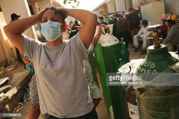 Relatives of COVID-19 patients queue to recharge oxygen tanks for their loved ones at the regional hospital in Iquitos, the largest city in the...