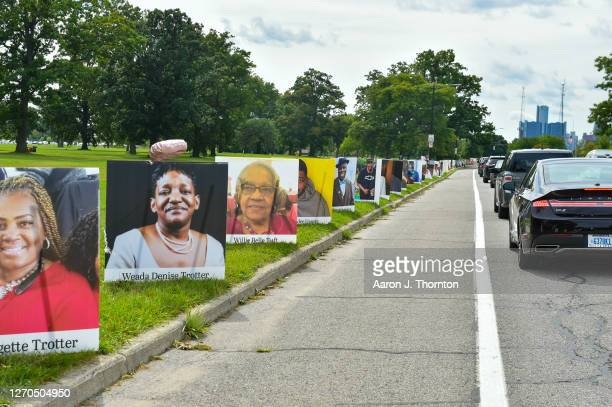 Relatives of COVID-19 victims drive next to the Images of the victims from Detroit displayed in a drive-by memorial at Belle Isle State Park on...