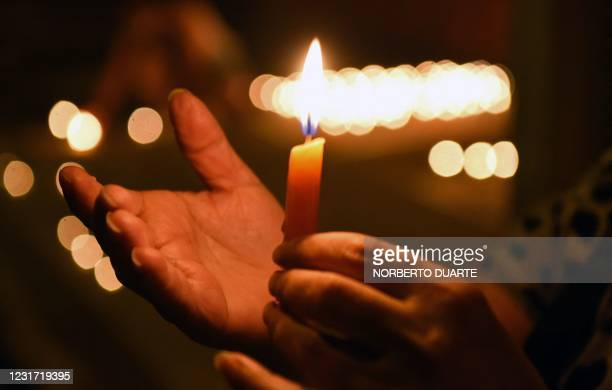 Relatives of COVID-19 victims light candles in front of the Health Ministry in Asuncion, in honour of the more than 3450 people who died from the...