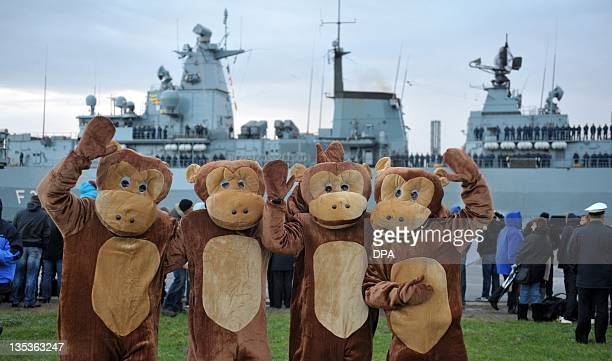 Relatives of crew members dressed as monkeys wave after the frigate 'SchleswigHolstein' of the Deutsche Marine German navy arrived at the naval base...