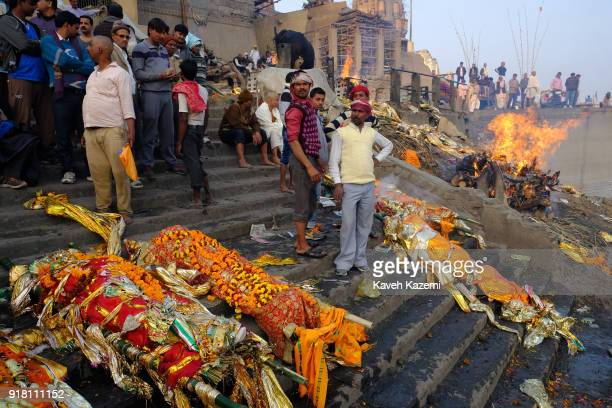 Relatives of deceased men wait on the staircase of Manikarnika Ghat to dip the bodies in Ganga River for a final purification act before the...