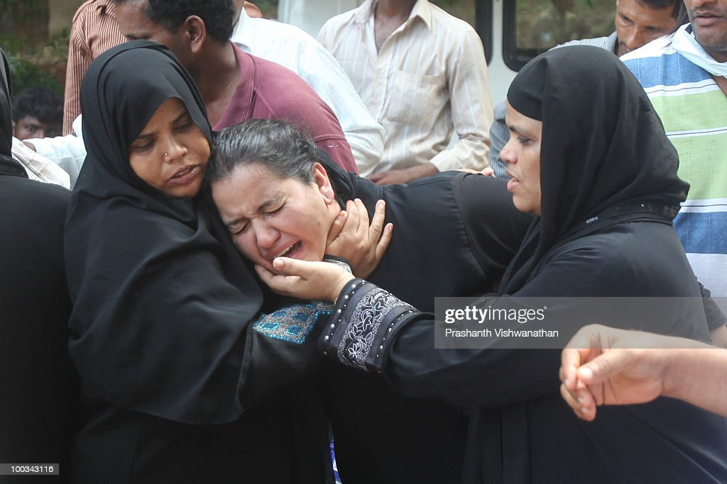 Relatives of deceased passengers break down outside a mortuary, after identifying their family members on May 23, 2010 in Mangalore. An Air India Express Boeing 737-800 series aircraft arriving from Dubai, with 166 people onboard, overshot the runway on landing in Mangalore and crashed into a forest. Airline officials say 8 survivors have been rescued with 158 others feared dead.