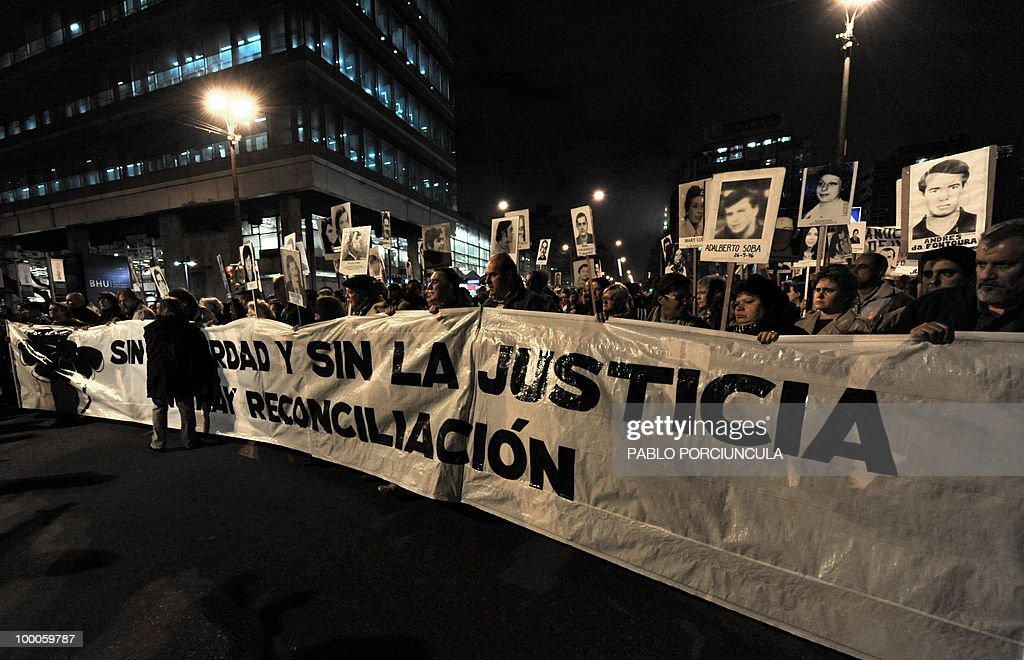 Relatives of disappeared people during the country's last dictatorship (1973-84) take part in the annual 'March of Silence' in Montevideo on May 20, 2010. The banner reads 'Without Truth or Justice, There is no Reconciliation'. AFP PHOTO/Pablo PORCIUNCULA