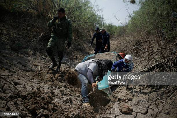 Relatives of disappeared people seek for human remains near the site where they found clandestine graves on June 19 2017 in Santa Elena at the...