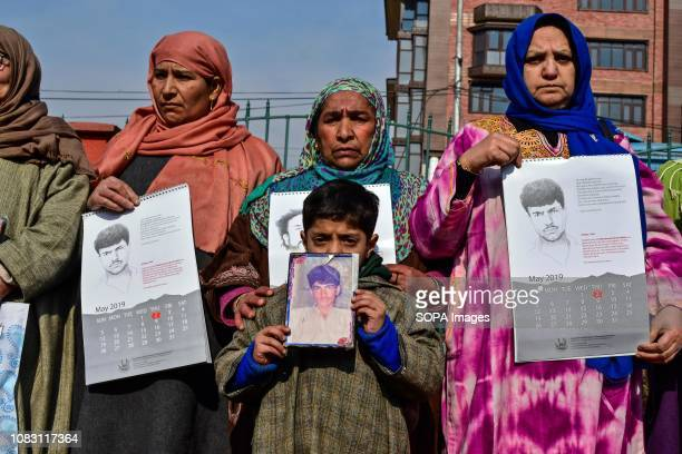Relatives of disappeared persons hold calendars and photographs of disappeared persons during a calendar release in Srinagar Indian administered...