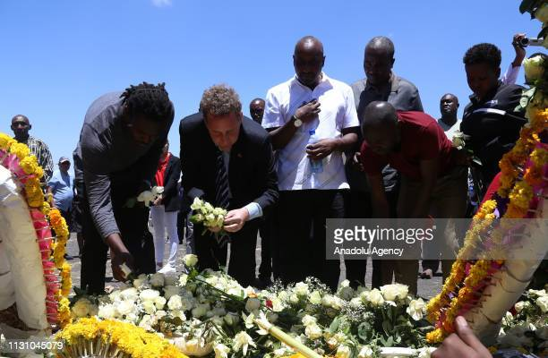 Relatives of Ethiopia Airlines victims who lost their lives in the crash place flowers at the crash site of Ethiopian Airlines Flight 302 in Addis...