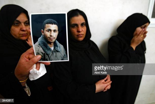 Relatives of Fadi AlAmoudi a militant from the Al Aqsa Martyr's Brigade hold up his picture in the family home April 17 2004 in Beit Lahyea Refugee...