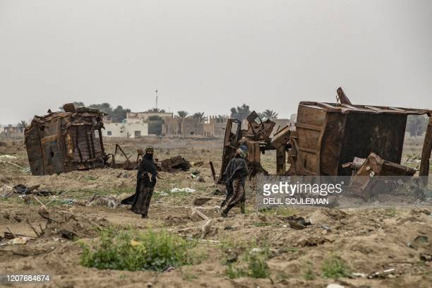 TOPSHOT Relatives of farmer Hamad alIbrahim clean his damaged land in the eastern Syrian village of Baghouz on March 13 a year after the fall of the...